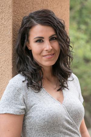 Author Jennifer Zeynab Joukhar, a portrait of her at work by Tina Case.